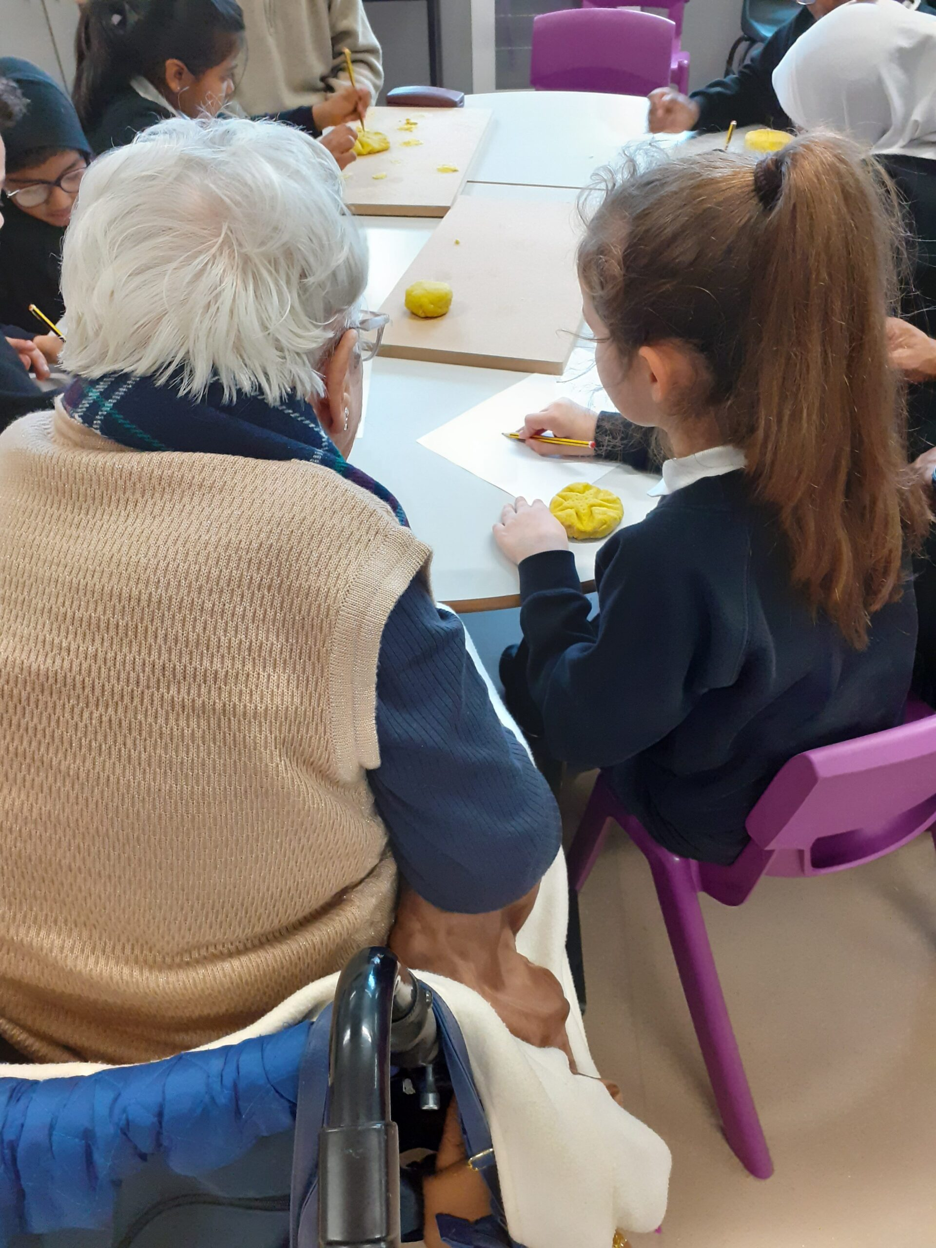 Intergenerational gathering at George Mitchell School as part of Tapestry Tuesday project part of Quality Street - pink chair