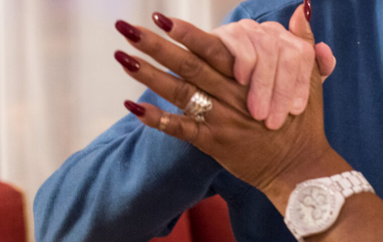 Photo cropped from a photo by Roxene Anderson showing the hands of a dancing couple, one of the hands is that of an old white man, the other hand is that of a young black woman with red painted nails, a gold wring and a silver watch
