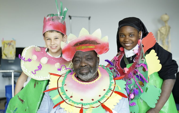 Quality Street - Our Celebration. photo by Chuck Blue Lowry. Showing three people dressed in carnival costumes. In the middle an older black man with a yellow and green carnival collar and red crown, behind him to the left a young boy with a red and yellow collar and red crown, to the right behind him a young black girl in a purple red and green costume with a black headscarf. They are all smiling.