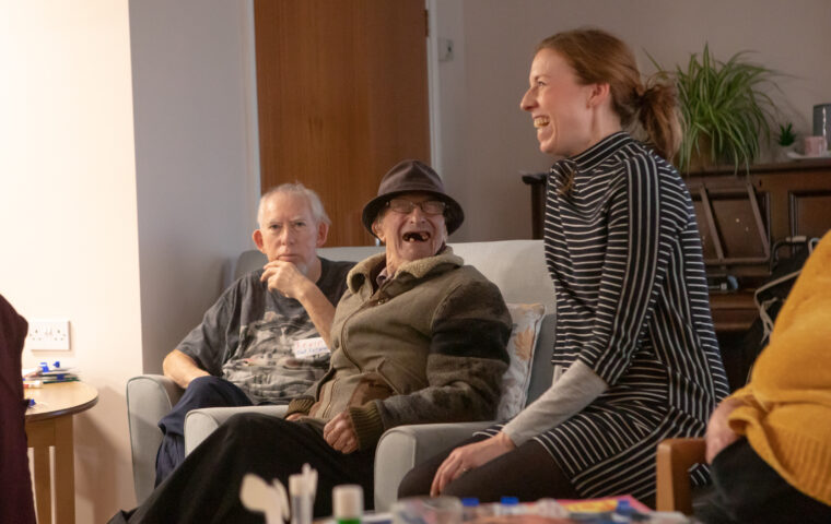 Inside Out 2019 photo by Jenna Selby shows three people sharing the joke, on the left in the background an older man sits in an armchair, just in front of him and older man in a heavy jacket and trilby hat laughs looking up at the young woman perched on the arm of a chair she is also laughing.