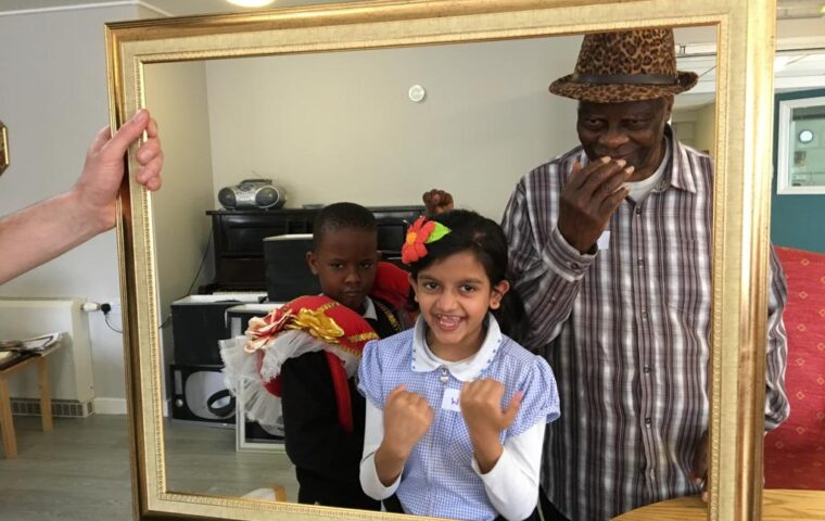 Quality Street - Wonderful Wednesdays - picture shows a hand holding a big gold frame, within the frame stand two children and an older black man, all three are laughing.