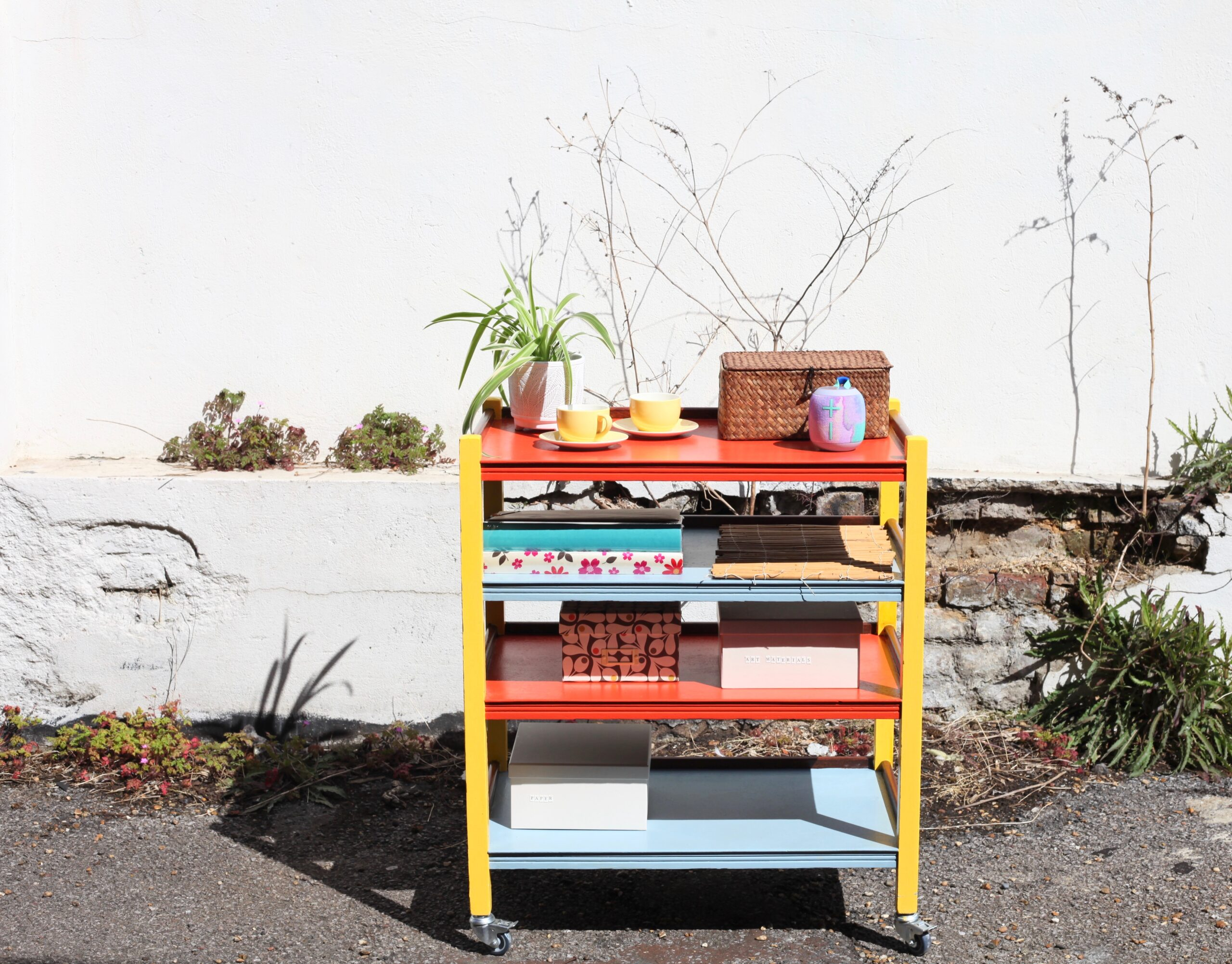 Picture shows a trolley with four shelves painted in bright colours and containing all sorts of exciting things including pot plants and a radio - this is Sandra, Agnes & Georgia's Entertainment Trolley, Work in Progress, for Inside Out 2021May 2021