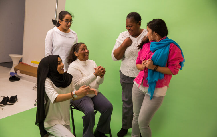 Picture from Decorum workshop shows a group of women against a green background. On the left a young woman in a white top and black headscarf is kneeling next to an older black woman who is sitting on a chair, behind them a young asian woman in a white top. Facing them standing is an older black woman with short hair in a white top, next to her a younger asian woman with a pink top and blue scarf, they are all smiling and laughing - photo credit Holly Falconer for Magic Me