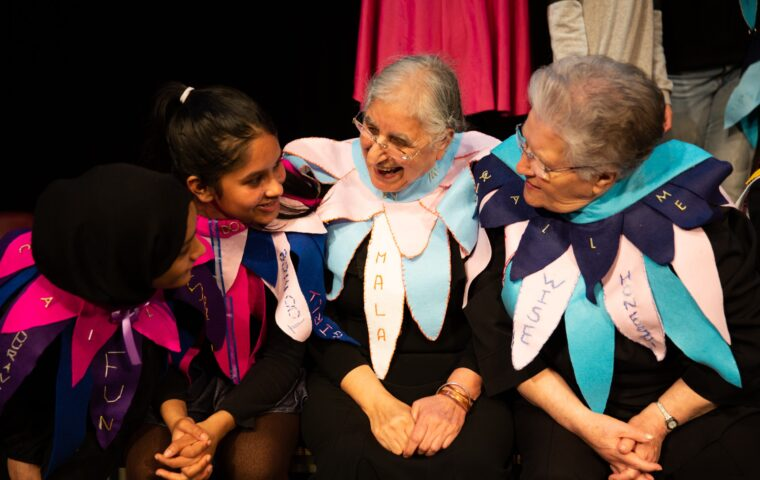 Picture shows participants at the In My Name showcase at Poplar Union. There are two younger women and two older women, all are wearing large collars made of felt pennants with words embroidered on them