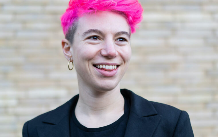 Photo of artist Lily Ash Sakula - photo shows a person (head and shoulders) with short bright pink hair, smiling, pale skin, wearing a dark top
