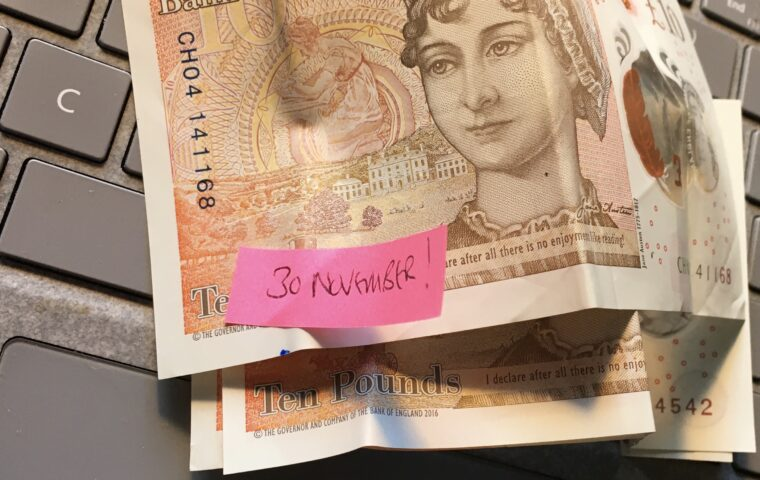 Photo showing three ten pound notes on a grey keyboard with the words '30 November' written on a pink post it stuck on top of the top note