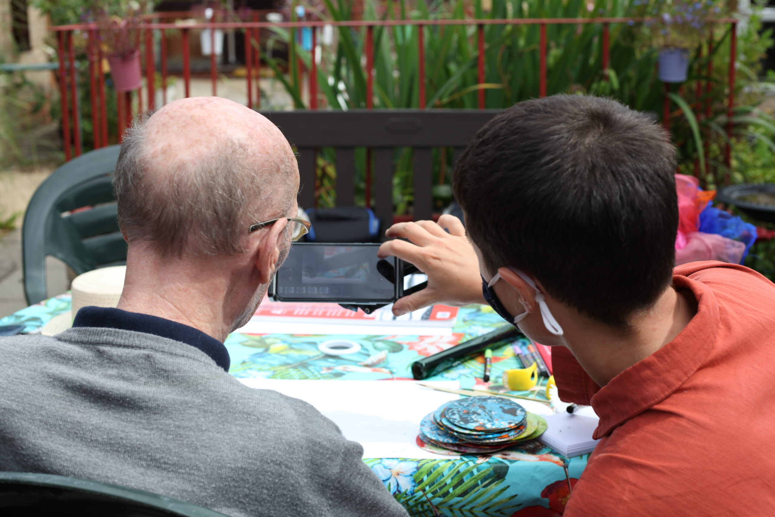 Photo shows two people looking at a mobile phone screen as they take a picture of an artwork they have just made. On the left is an older man with his back to us, he is wearing glasses and a grey top, on the right is a younger man with dark hair, he is holding the phone and is wearing an orange top. In front of them is a table covered with a colourful table cloth and art materials.Essex 2021 Magic Me Workshop 1 Quenby_Photo Credit Georgia Akbar & Lily Ash Sakula