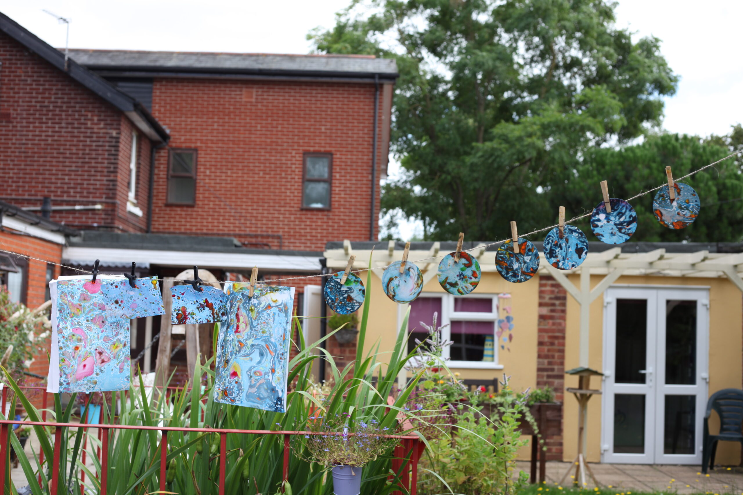 Photo shows the garden of a care home, across the garden is a washing line holding up different pieces of marbled paper - some are square and some are round - they are mostly dominated by blue colours Essex 2021 Workshop Quenby__Photo Credit Georgia Akbar & Lily Ash Sakula.jpg (1)